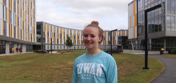 Elizabeth Hudak stands in front of Holly Pointe Commons at Rowan University with the building behind her