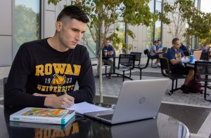 Rowan marketing major Marko Minic studies outside by the Rohrer College of Business.