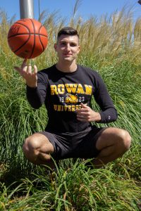 Marko spins a basketball while standing in the grass outside the Rec Center