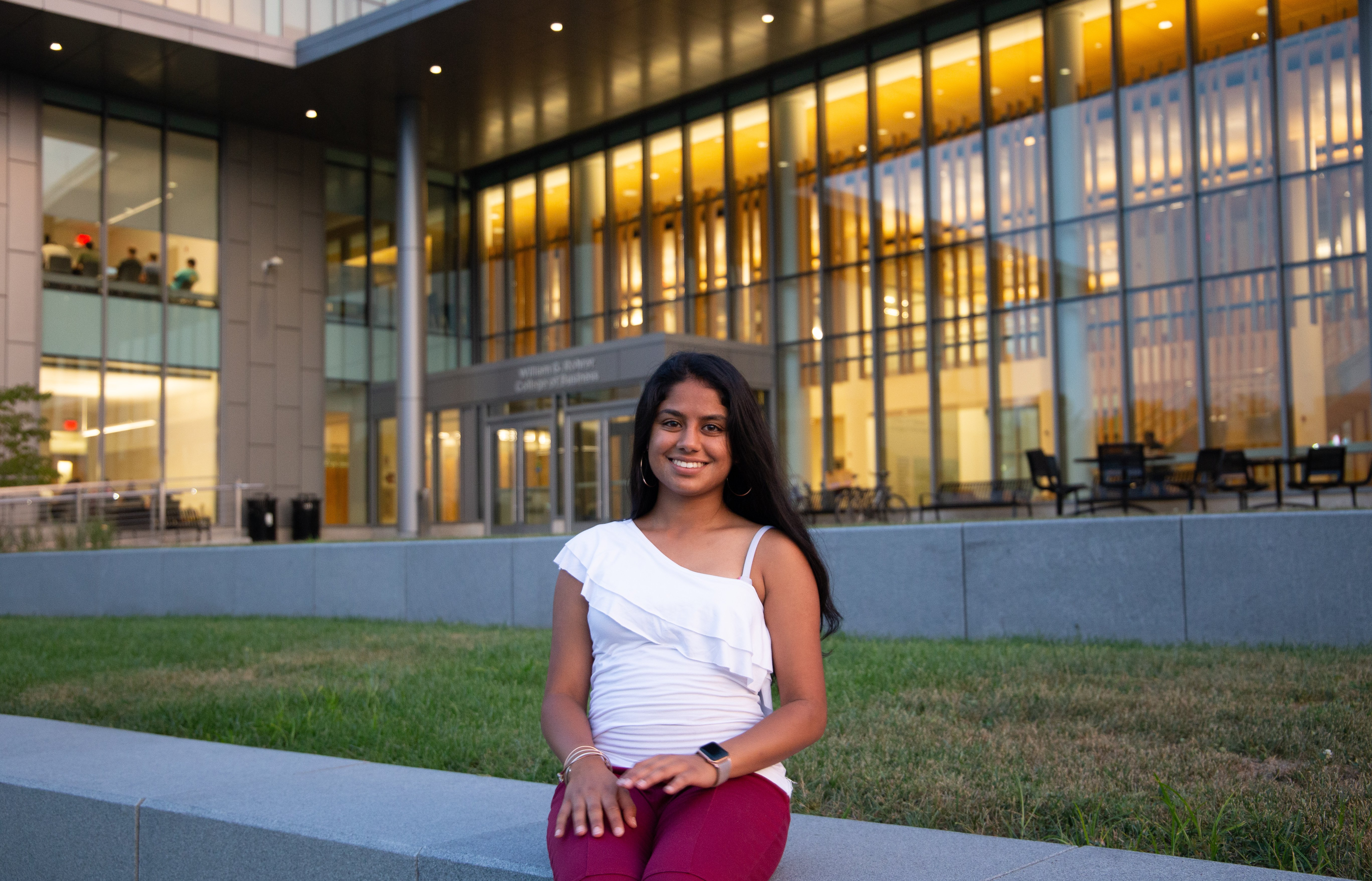 Shreya Shah sitting outside of Rowan University's Business Hall.