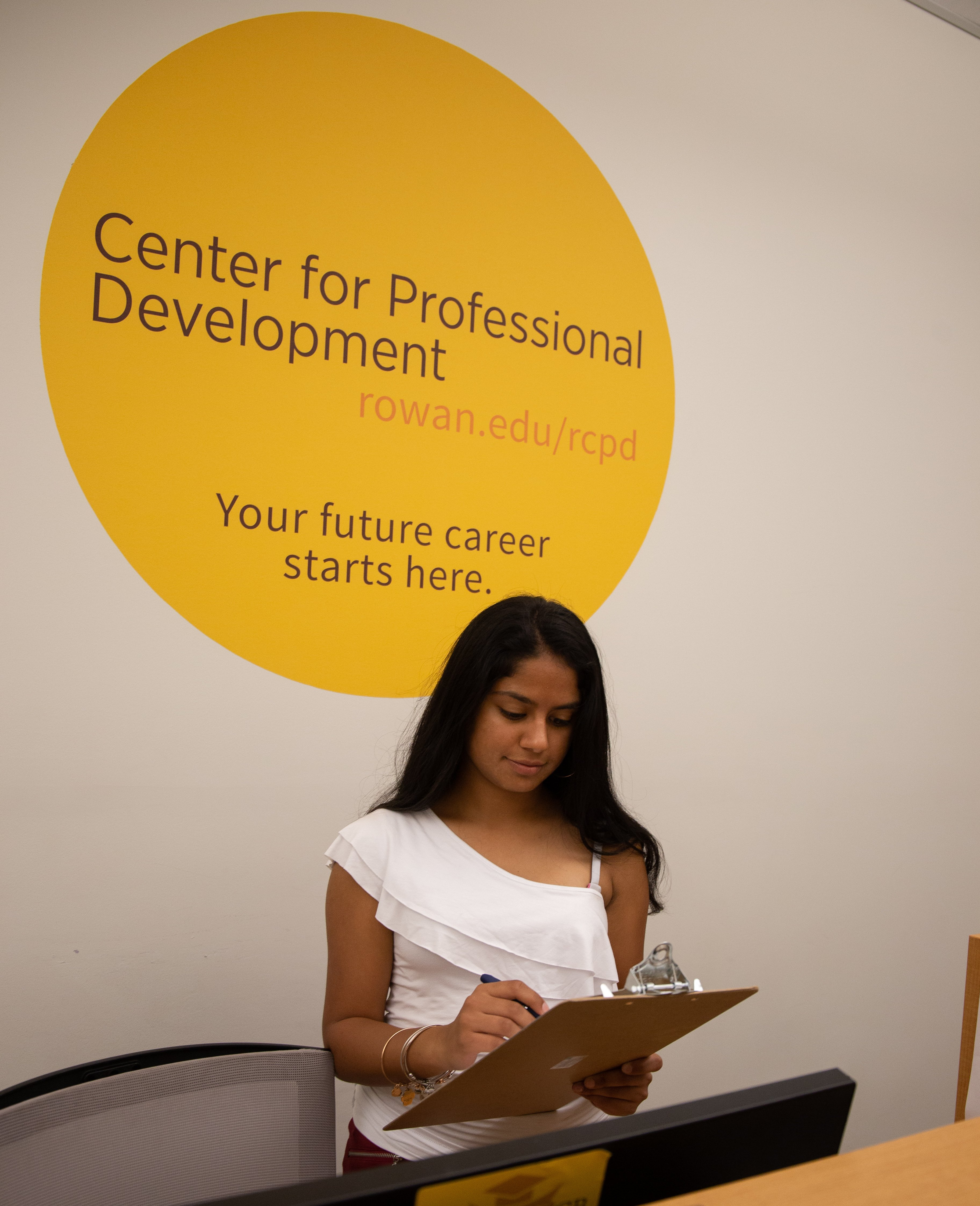 Shreya Shah reading off of a clipboard in the Center for Professional Development.