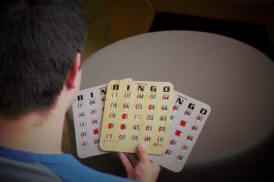 RAH Programming Coordinator Joseph Scafiro holds bingo cards, one of the activities offered at Rowan After Hours.