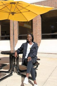 Mary Gomez, an international student and Community Health major, sits outside the Chamberlain Student Center