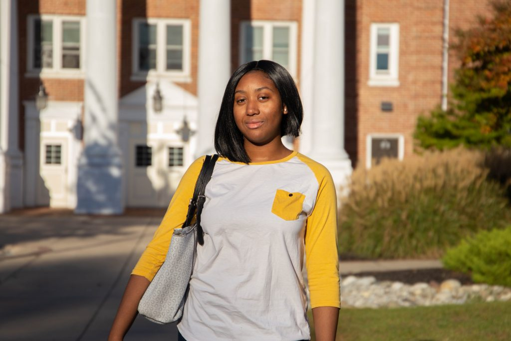 Dana Fenton, a Biochemistry major and Rowan freshman, stands in front of a residence hall