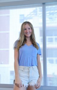 Erin DeBiasse, a Marketing and Supply Chain and Logistics major, stands in front of a sunny backdrop