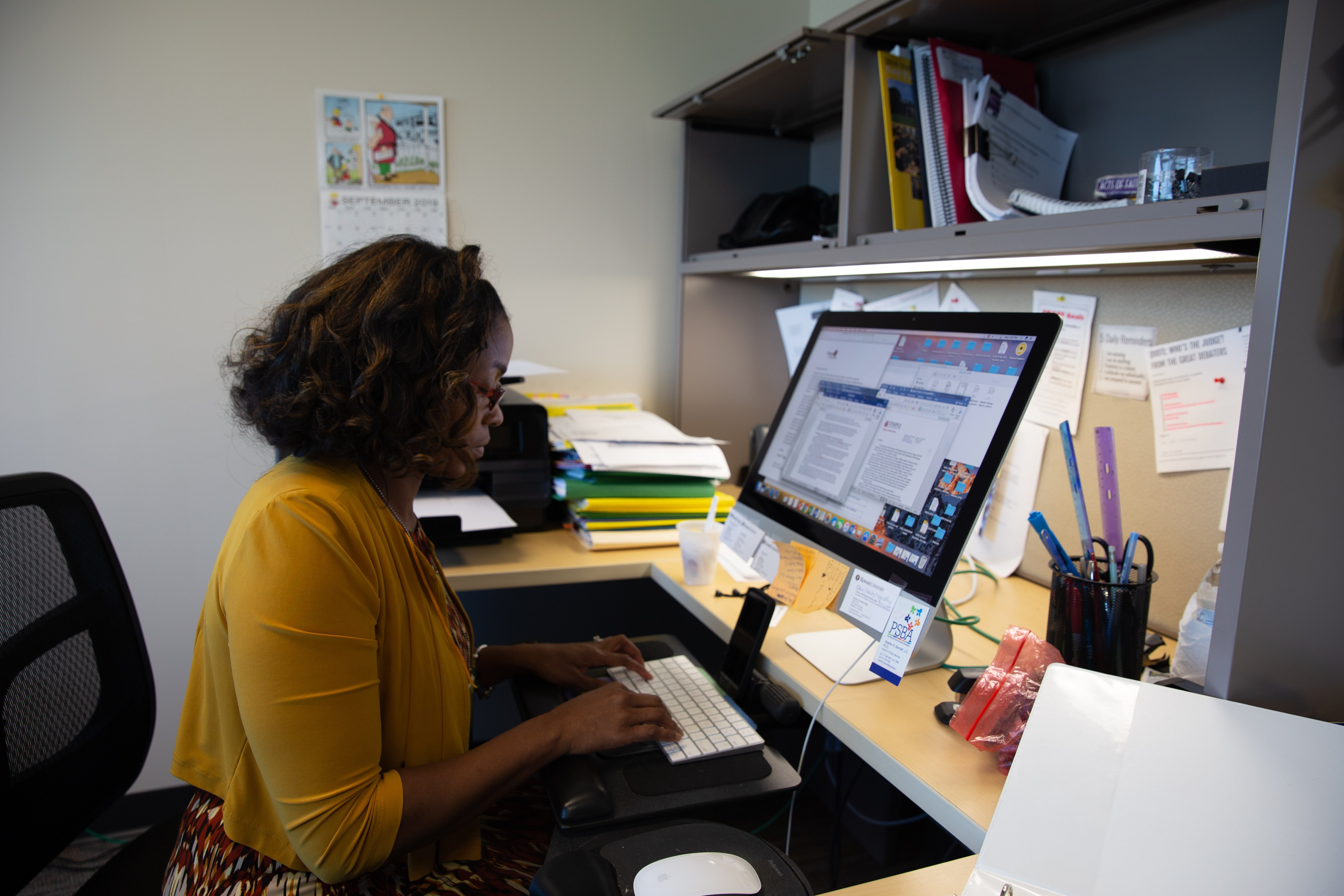 Dr. Angela Beale-Tawfeeq typing at her desk.
