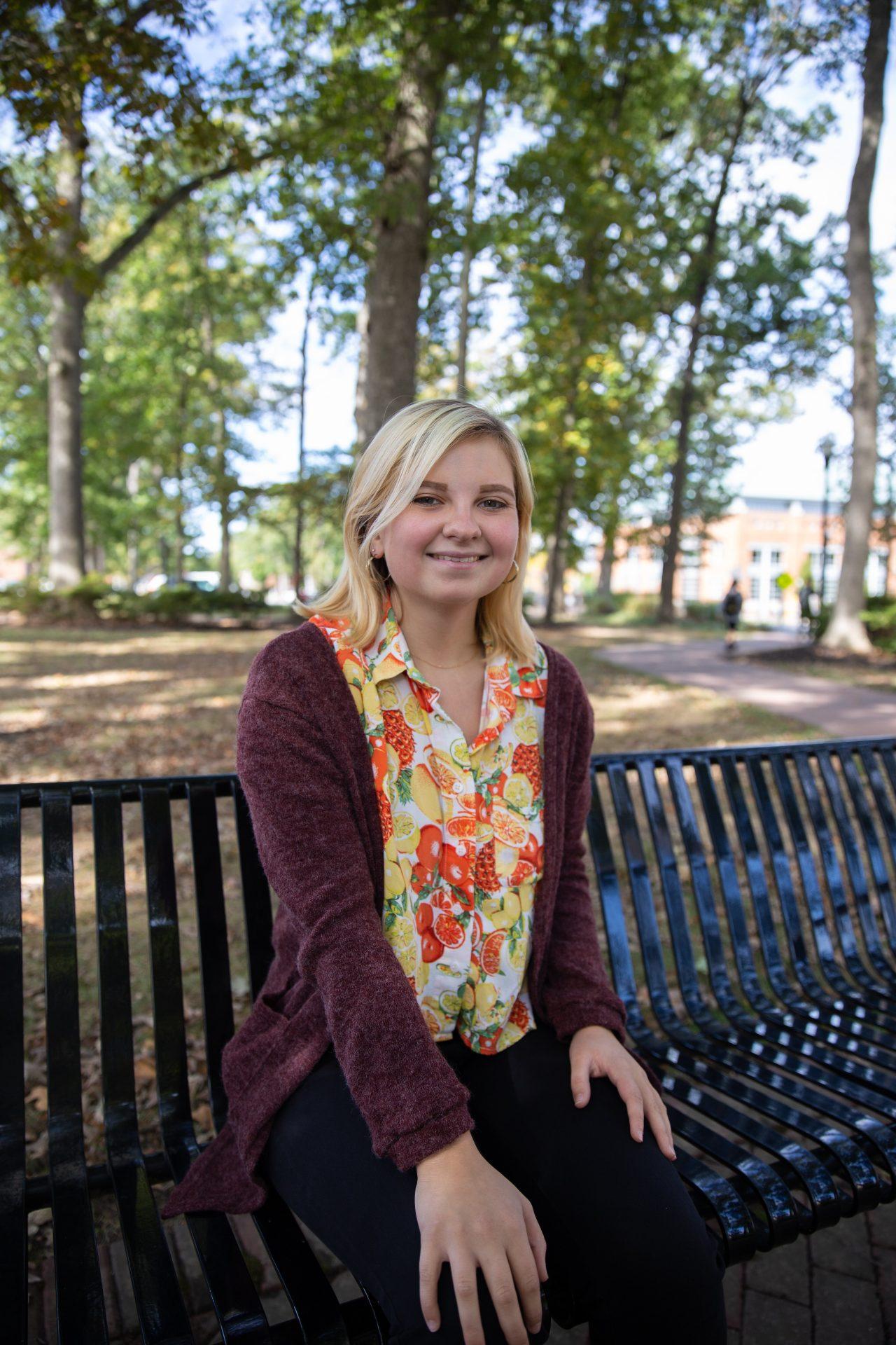 Grace Van Cleef posing on a bench on Rowan University's campus.
