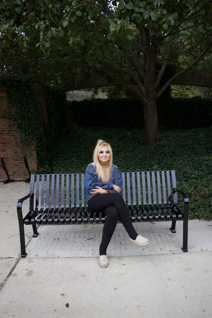 Radio/TV/Film major Emma Shea sits on a bench on Rowan's campus