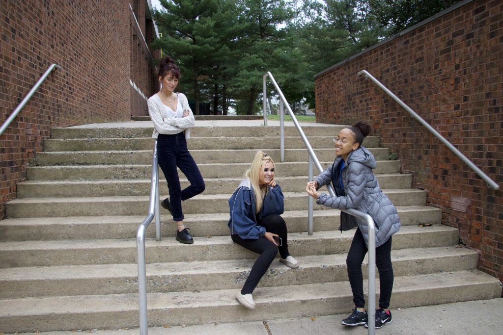 Three freshmen students and friends hang out on steps outside on Rowan's campus