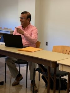 Rowan Ed.D. student Ketan sits at a desk with his laptop open, smiling.