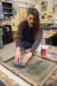 Leann using art supplies to make a screen printing in the studio at Westby Hall at Rowan University.
