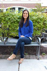 Rowan alumna Jennifer Chin, a biochemistry major, sitting outside on a bench on Rowan Boulevard