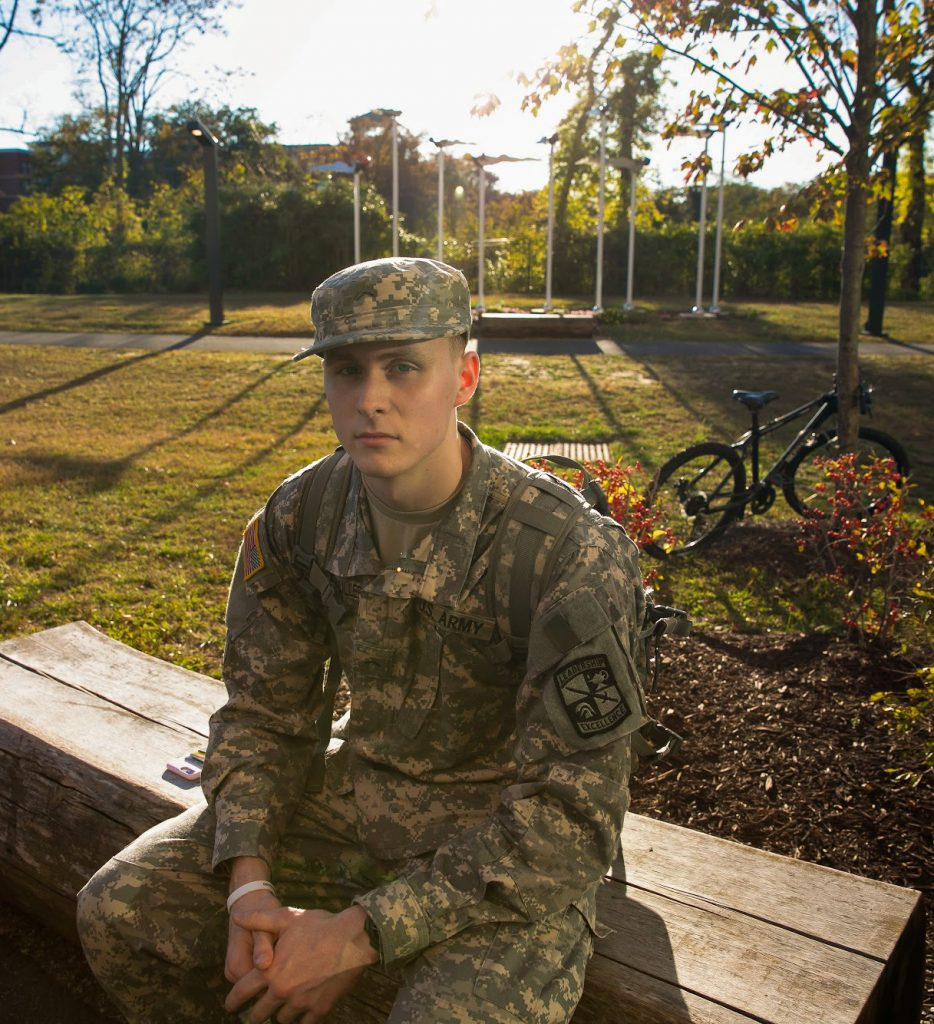 Gregory Werthmuller, Exercise Science major and Rowan freshman, sits on a wooden bench on campus