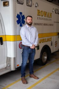 Jeff Dever, an alumnus of the Disaster Preparedness and Emergency Management program, stands in front of a Rowan University EMS truck.