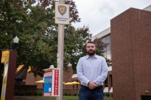 Jeff Dever, an alumnus of the Disaster Preparedness and Emergency Management program, stands proud with one of the HeartSafe Campus stations he helped bring to Rowan.