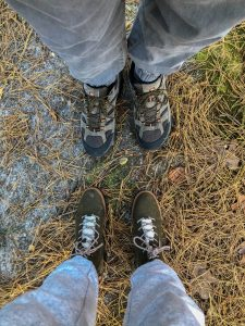 Two pairs of hiking boots facing each other on a nature trail.