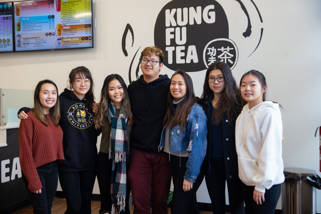 Seven friends and members of the VSA eboard stand together at Kung Fu Tea on Rowan Boulevard