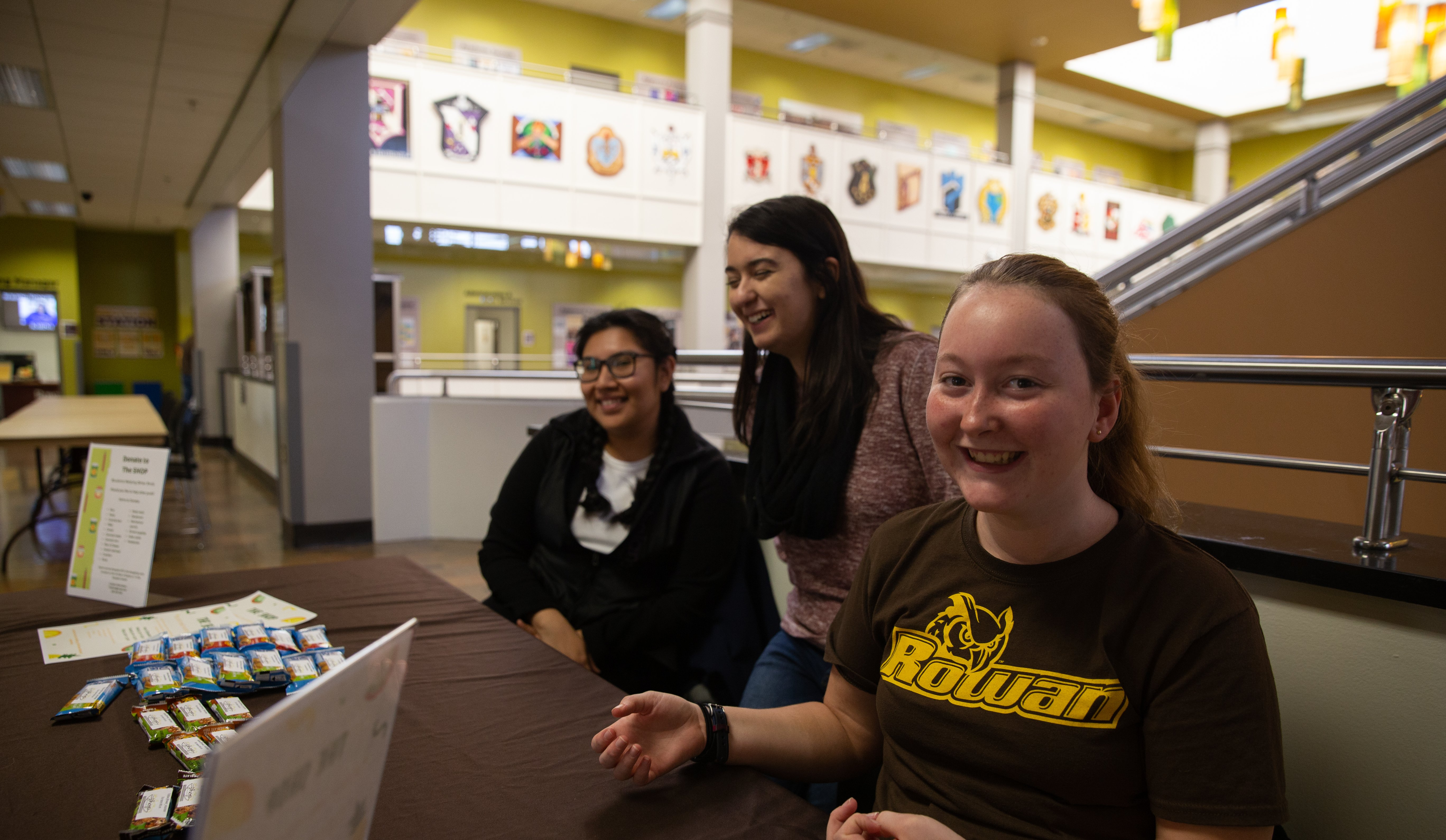 Rachel Rumbsy (right) hands out granola bars at Rowan University's Student Center for The SHOP.