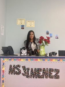 "Rowan Ed.D. student Manuela sits at a desk with the name ""Ms. Jimenez"" in colorful letters pasted to the front of the desk."