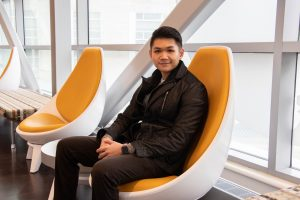 Thai sits in a round orange chair in the bridge connecting the two engineering buildings at Rowan University.