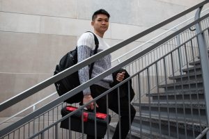 Thai is pictured behind a handrail as he walks up the steps holding a red and black toolbox .