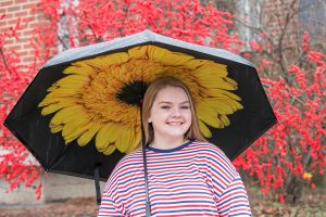 Cassidy holding a sunflower umbrella by red foliage.