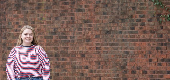 cassidy stands in front of a brick wall.