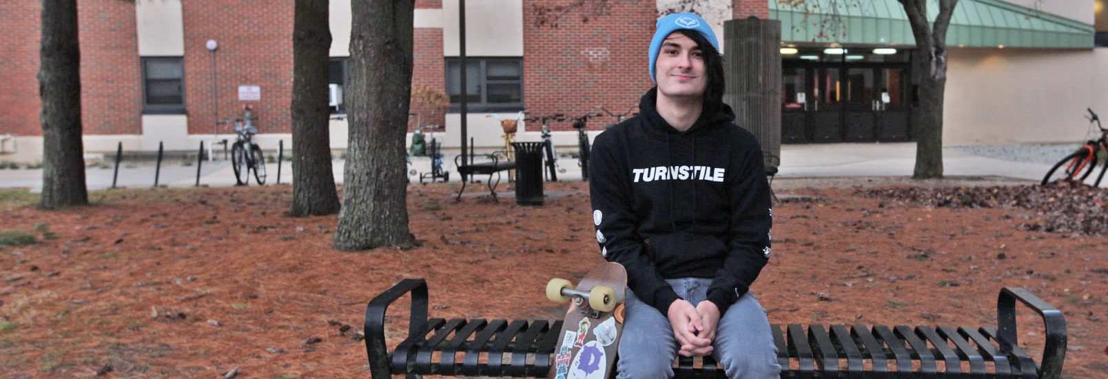 Freshman Music Industry major Devin Saienni sits on a bench on campus