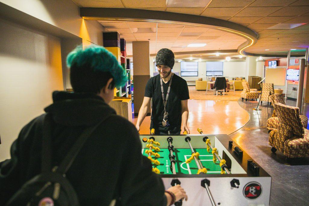 Matt playing foosball in the rowan university game room.