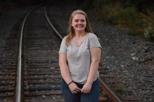 Cassidy posing for a portrait on train tracks