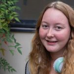 Freshman Public Relations major Rachel Rumsby sits on a bench outside on Rowan's campus.