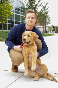 Piano Performance major Ben holds Zazu, a golden retriever puppy, in his lap outside