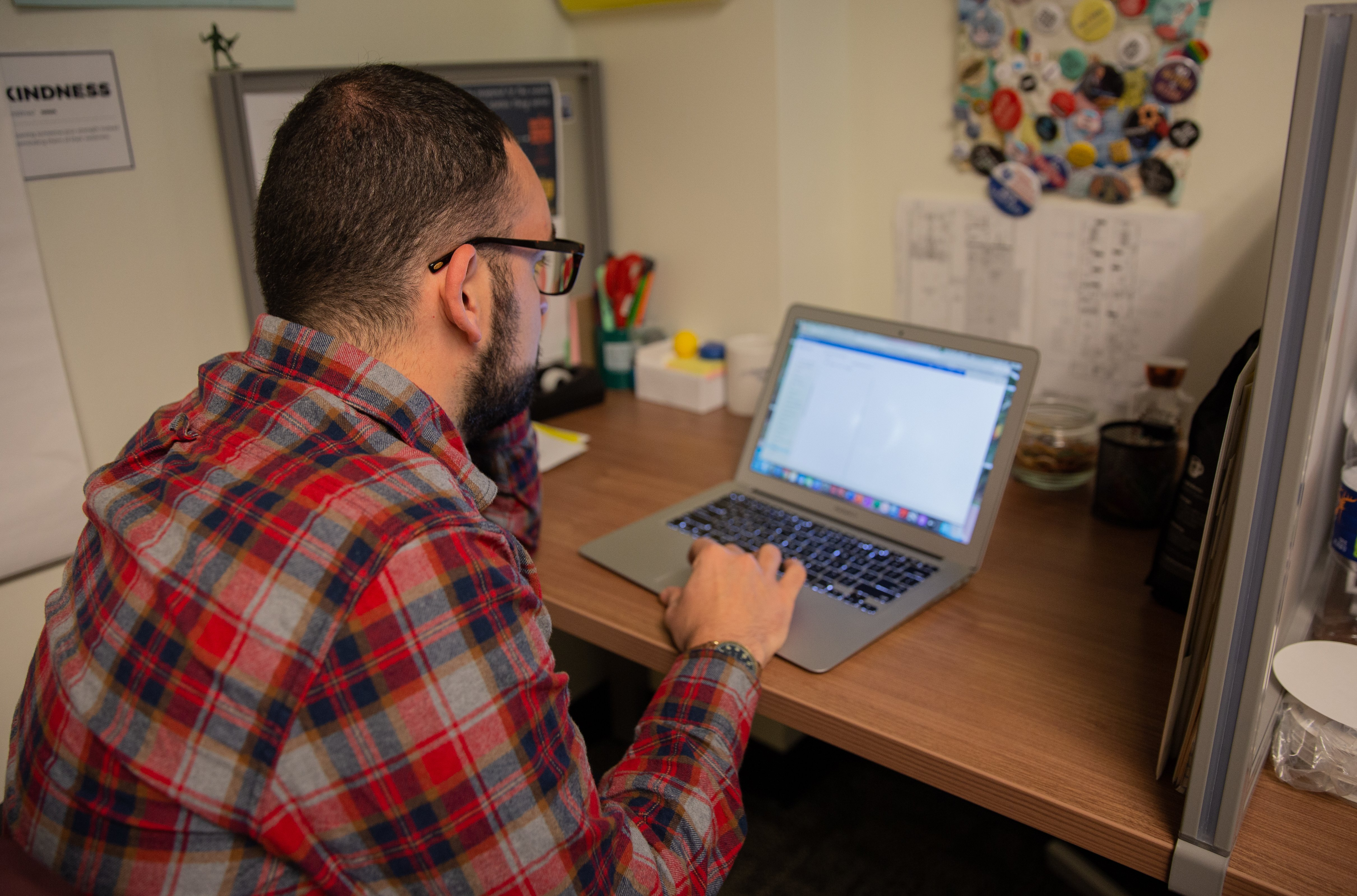 Rowan PhD student Donn Garby working at his cubicle in Hawthorne Hall.