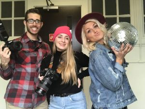 Alex, Nicole, and Vanessa stand together holding their cameras and a disco ball.