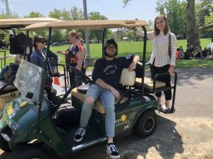 Dean sits in the front seat of a golf cart, while Alyssa stands on the back bumper.