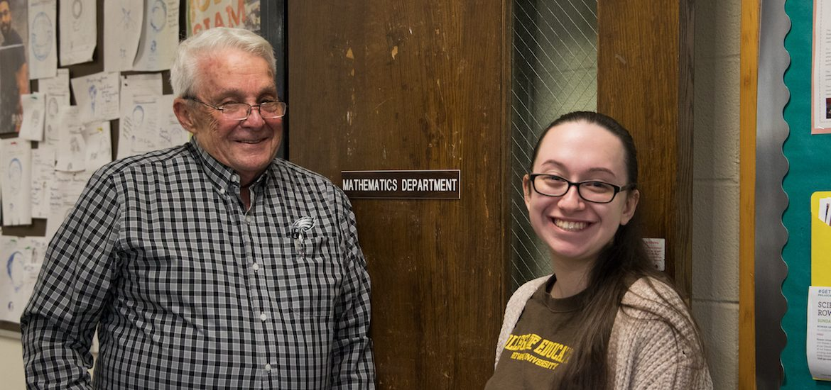 Adriana and Professor Smith smile in front of the Mathematics suite.