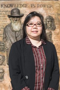 Dr. Anna Sun stands in front of the James Hall statue