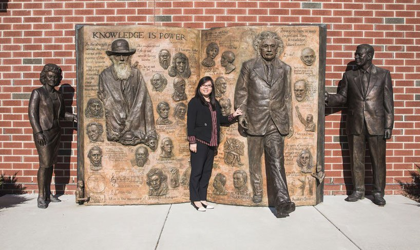 Dr. Anna Sun stands in front of a bronze statue outside of James Hall