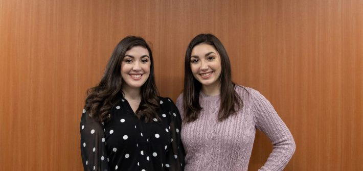 Sisters Sophia and Madison Agostini pose in front of a wood panel wall.