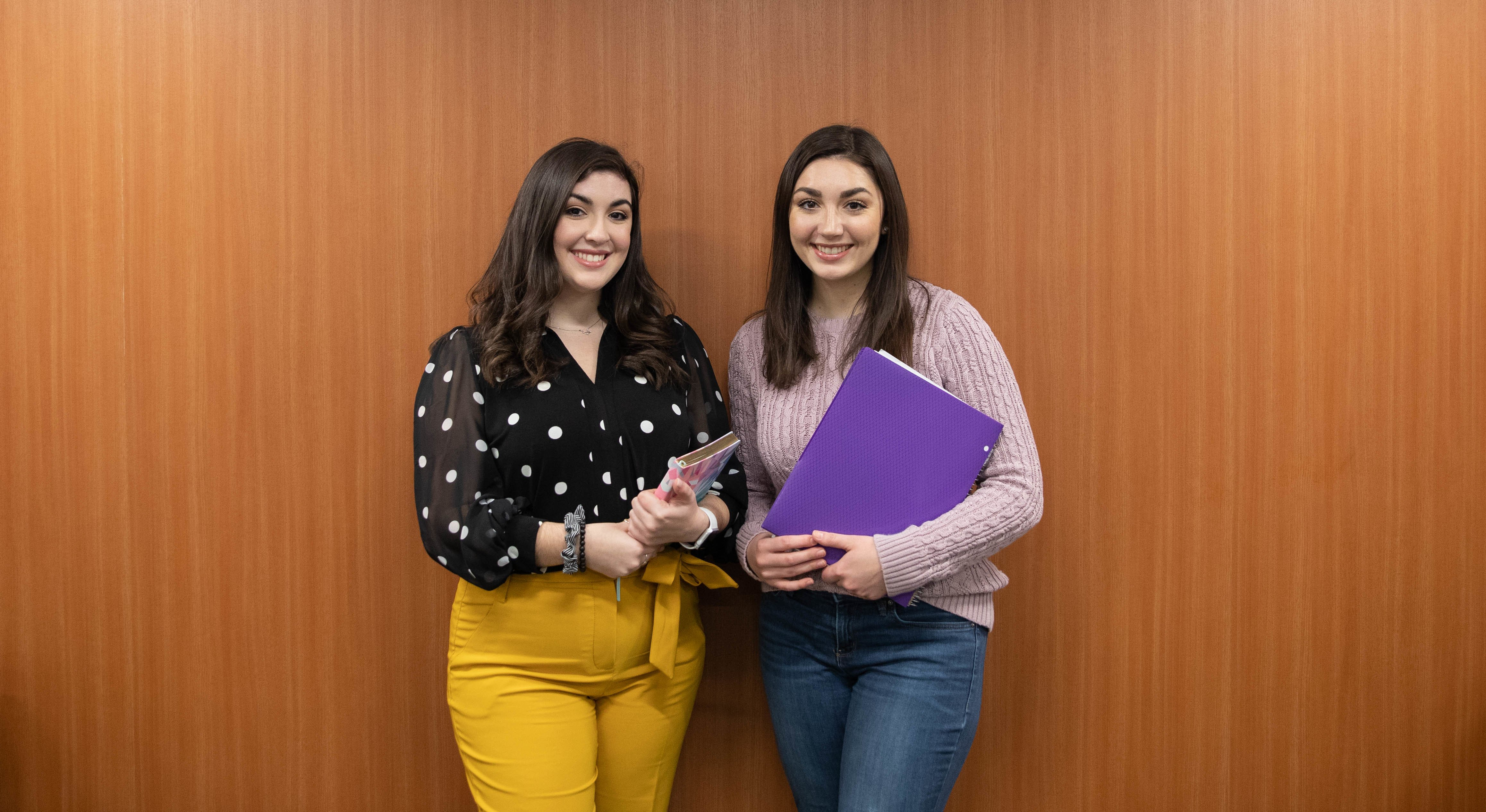 Sophia and Madison pose with school supplies in front of a wooden background.