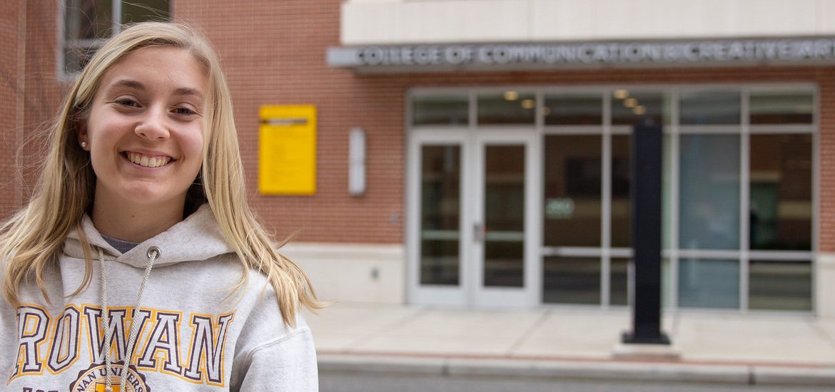 Communication Studies major Ashley Davis stands in front of Victoria Hall