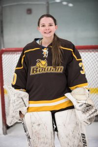 Emily is wearing her ice hockey uniform, standing in front of the goal net.