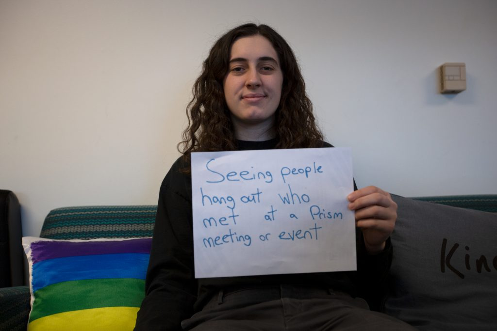 """Abby holds sign that says """"Seeing people hang out who met at a Prism meeting or event"""" as a joy for her."""