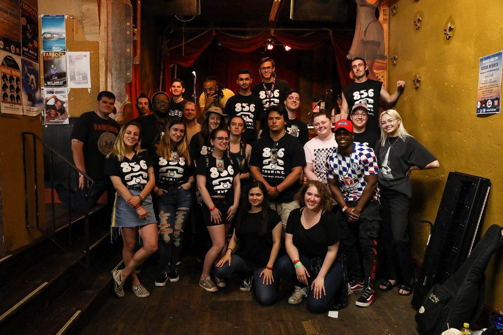 A group of approximately 20 Rowan students grouped together inside a concert venue.