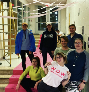 Jessica wears a Women of Westby t-shirt and stands with her peers in Westby Hall, as they prepare an installation.