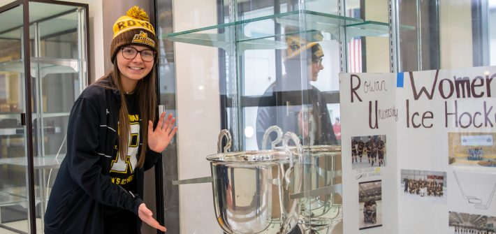 Emily stands in front of the women's ice hockey trophy.