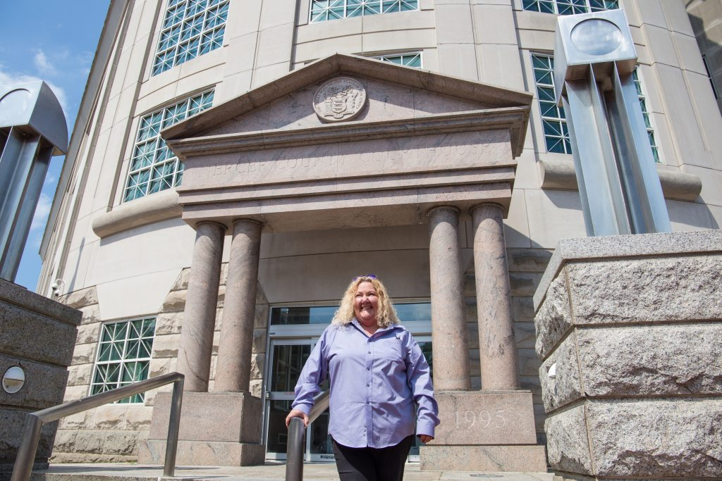 Kristen Cunningham stands outside the concrete building of the Mercer County Courthouse on a sunny day
