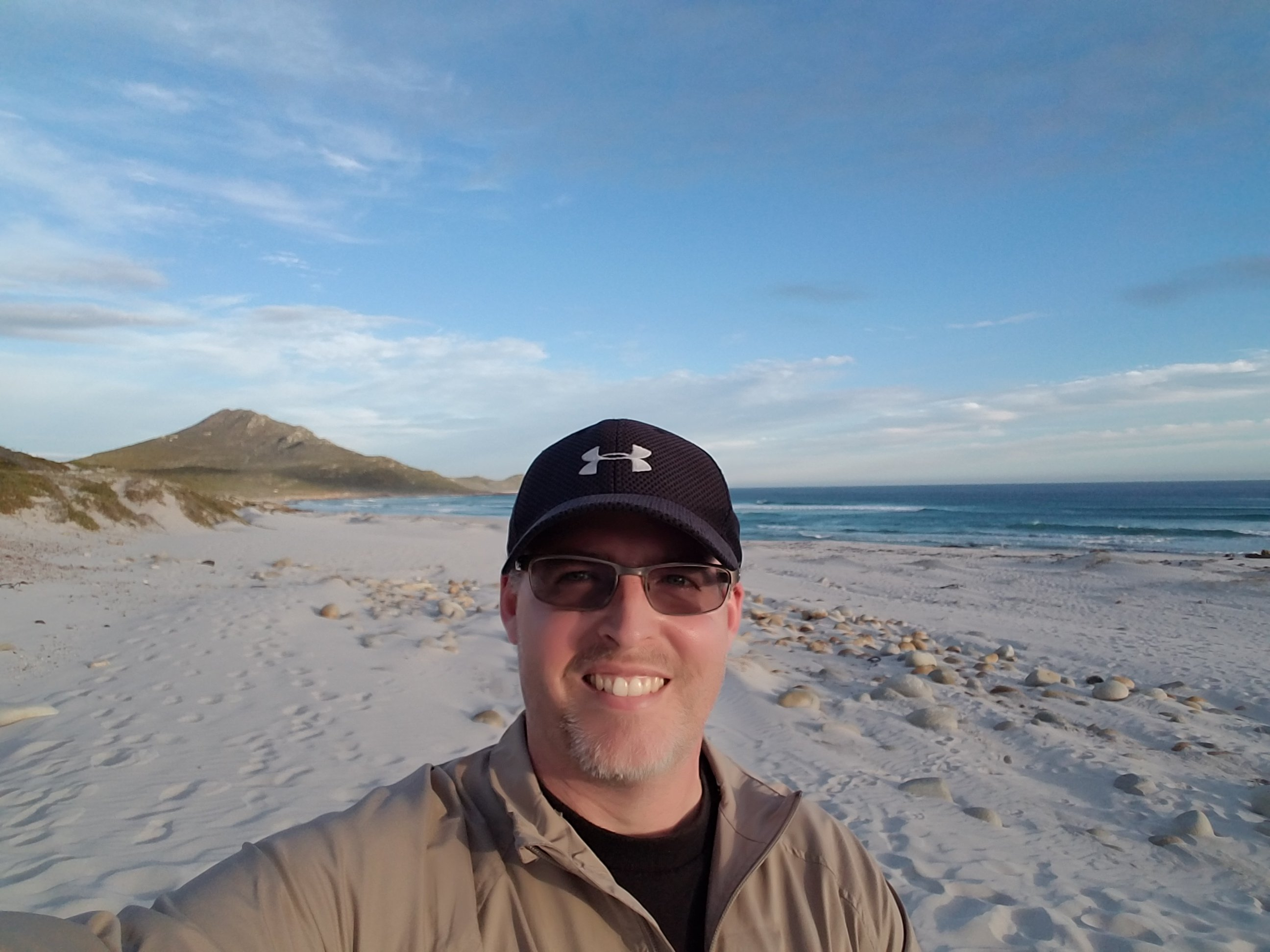 Chris Dromgoole smiles for a selfie on the beach.