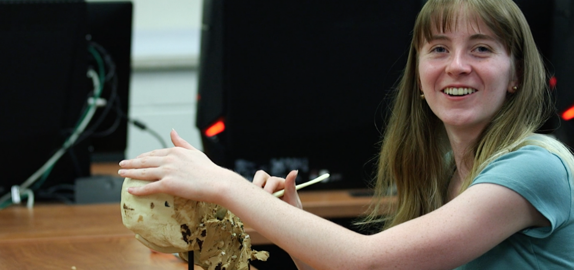 Emily carving a clay skull in a classroom.
