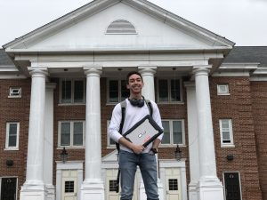 ,JT poses in front of Chestnut Hall with his laptop and headphones.